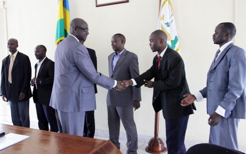 Minister Busingye congratulates court bailiffs and notaries after a  swearing in ceremony in April this year. (Net photo)
