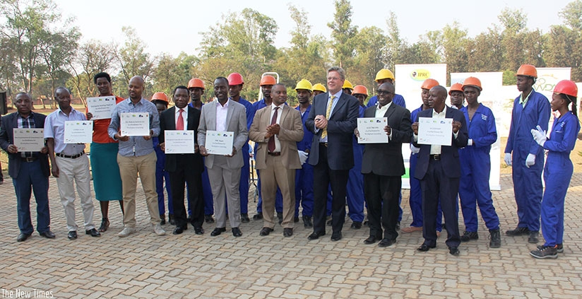 Rwamukwaya (6th Left) and Amb. Dr. Woeste (3rd Right), construction companies' managers and apprentices pose for a group photo after the event. (Courtesy)