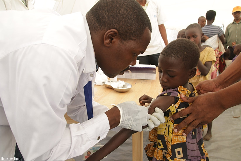 A doctor immunising a child. Children; make sure you always tell your parents if you feel sick so they can take you to the doctor. / ©UNICEF Rwanda/2015/Pflanz