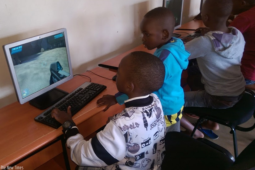 Young boys share skills on how to play computer games. Use the computer to search for educative information. (Dennis Agaba)