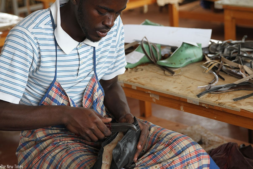 A worker makes a shoe at Masaka Business Incubation Center. File