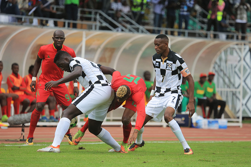 1521322837Defender-Herve-Rugwiro-battles-for-the-ball-with-Naby-Soumah-during-the-match-as-captain-MIGGI-looks-on