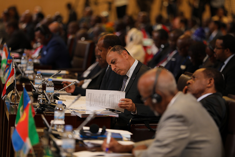 1521500559A-delegate-reads--through-documents-at-the--Executive-council-of-ministers-of-African-Union-meeting-in-Kigali