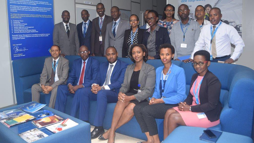 Senior managers at the airline join the incoming and outgoing CEOs in a group photo after Makolo took over from Ndagano. State minister Uwihanganye is third from left (seated). / Courtesy