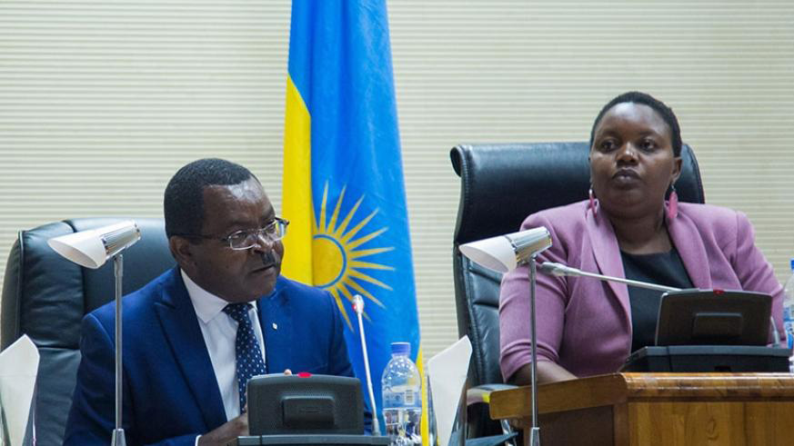 The Minister for Trade and Industry, Vincent Munyeshyaka (Left), addresses parliamentarians as the Deputy Speaker in charge of Legislation, Jeanne d'Arc Uwimanimpaye, looks in a recent plenary session. / File.