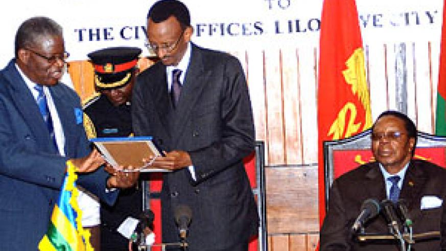 President Kagame receives the declaration conferring on him the Freedom of the City of Lilongwe from Professor Donton Mkandawire, the Chief Executive of Lilongwe City Assembly. Seated is Malawian President Bingu wa Mutharika. (Photo/PPU)