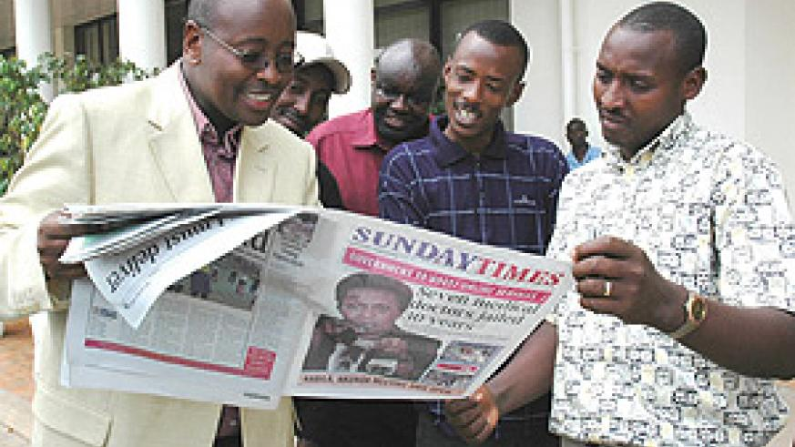 Musoni (left) and journalists peruse through a Sunday Times copy yesterday after the town hall meeting on media. (Photo/ J Mbanda)
