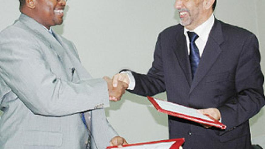 Musoni (L) and Abdulbaset exchange documents after signing the Rwandatel deal yesterday at Finance Ministry offices.