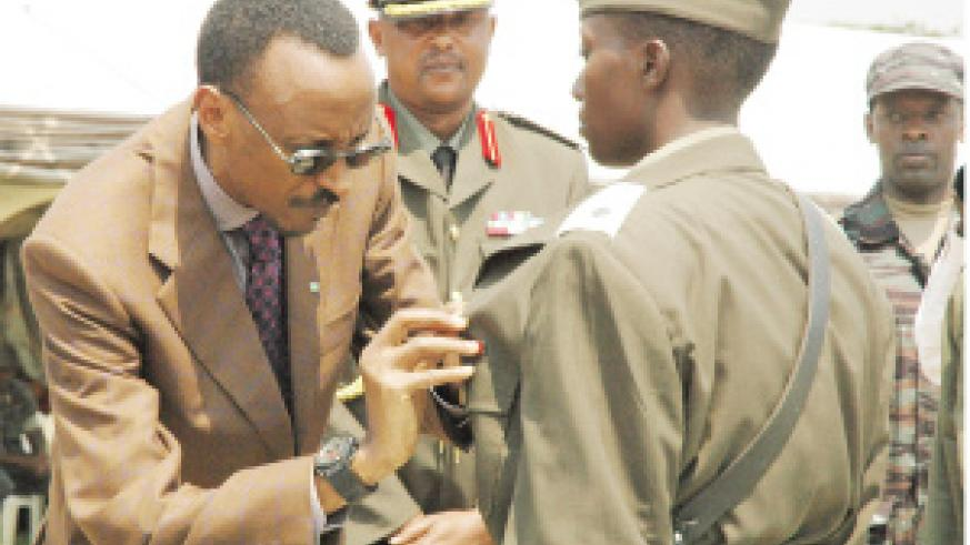 Kagame decorates 2nd Lt. Jacqueline Uwamahoro, who emerged the best officer cadet during the just concluded course at Rwanda Military Academy, Gako, yesterday. (Photo/G. Barya)