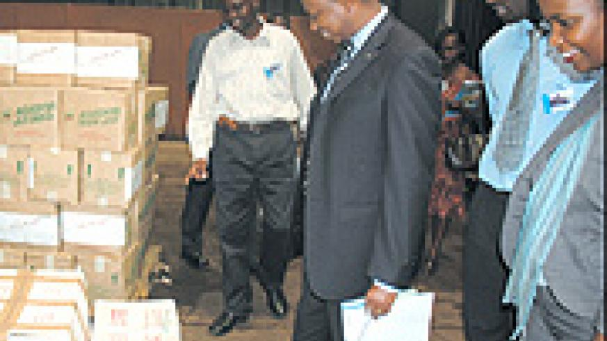 Minister Vincent Karega (center) inspects goods in a bonded warehouse.
