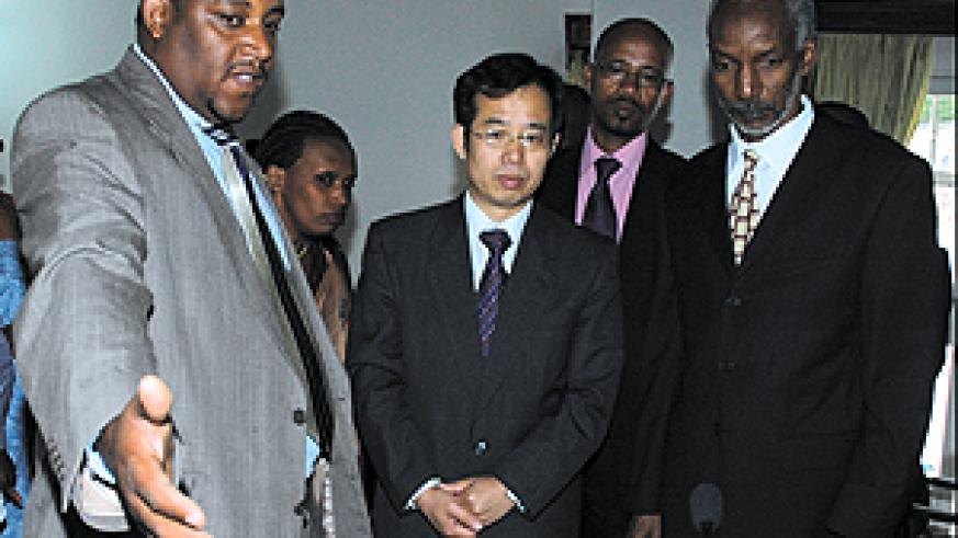 RPF's Secretariat ICT Officer, Eric Gasana (left) showing the Chinese Ambassador to Rwanda Sun Shuzhong (centre) some of the equipment donated to the party after the handover function in Kimihurura yesterday. (Photo/ G. Barya)