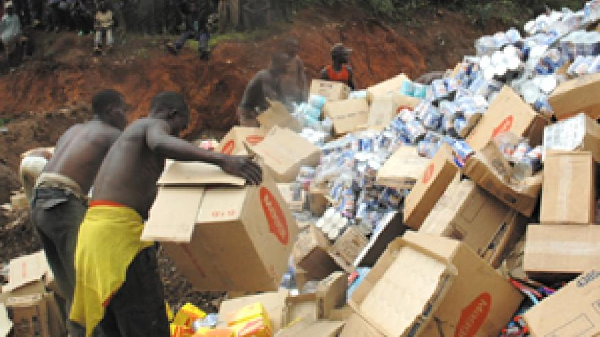Street boys look on as expired foodstuffs from BENALCO are destroyed at Nyanza in Kicukiro on Wednesday. (Photo/ J. Mbanda)