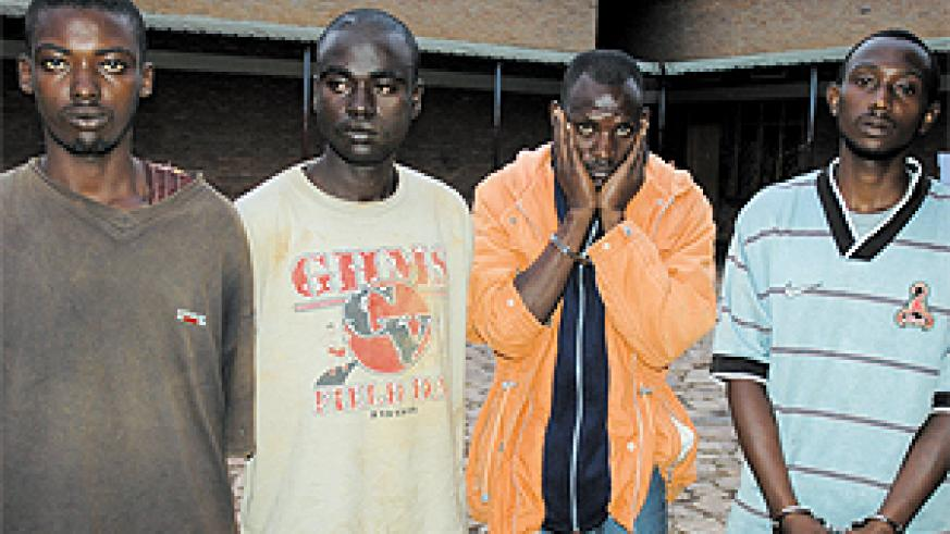 (L-R) Emmanuel Uwayisaba and Jean Baptiste Yafashije, the murder suspects, and their colleagues who were reportedly looking for clients for the victim's car, at Remera Police Station, yesterday. (Photo/G. Barya)
