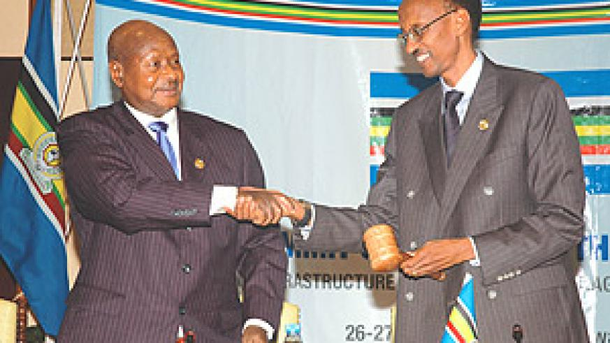 President Kagame receiving the instruments of power from out-going Chairperson of the EAC, Uganda's President  Yoweri Museveni.