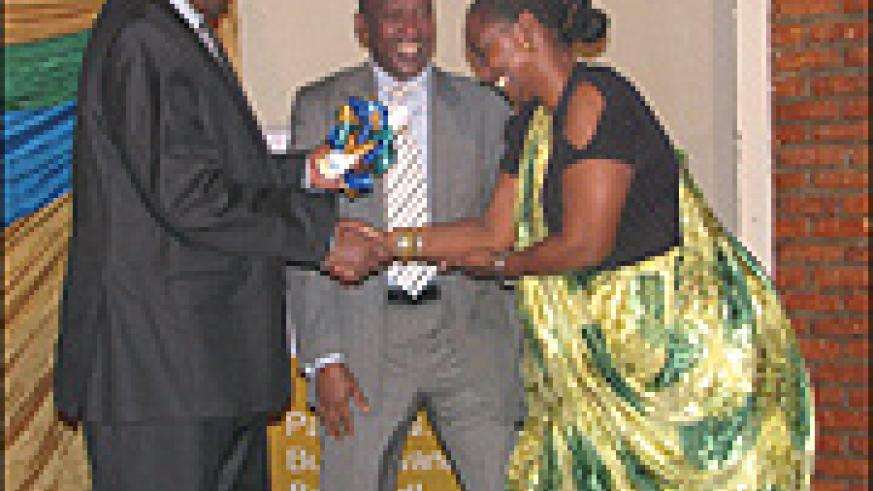 James Musoni, Finance and Economic Planning Minister (L) awards a certificate of recognition to Mary Baine, Rwanda Revenue Authority (RRA) Commissioner General for heading the tax body for a decade. Looking on is Ephraim Turahirwa, Chairman board of Direc