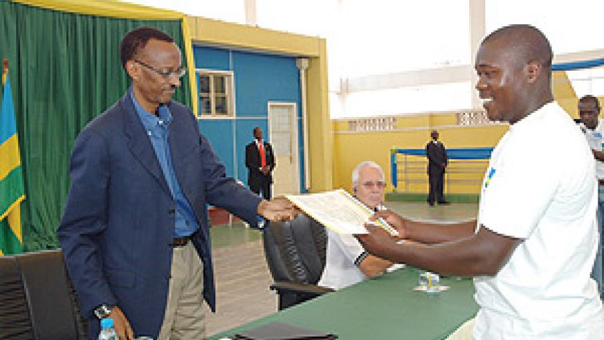 President Kagame giving an award to one of the people recognised for excelling in Ubudehe, Vianney Sebatwa. (PPU photo)
