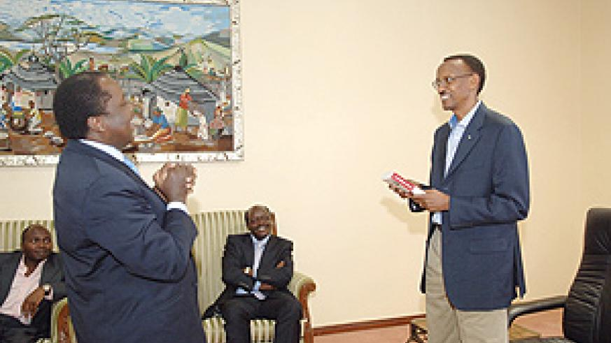 President Kagame receives a book from Mugo Kibati, former chief executive of East Africa Cables during a courtesy call by a group of Kenyan professionals who have formed an investment vehicle based in Rwanda. (PPU photo).