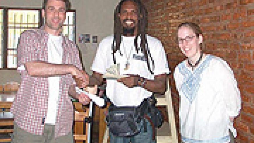 One Love Project coordinator, Gatera Rudasingwa receive funds from MBCBC coordinators Darryl R. Towers and Meredith Daun.(File photo)