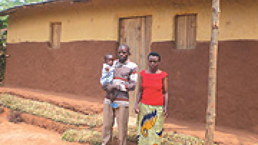 Harerimana and his wife with one of their two kids in front of their new house. (Photo/ B. Asiimwe)
