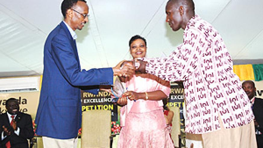 WELL DONE: President Paul Kagame handing over a trophy to the best coffee farmer at the Cup Of Excellence awards. (Photo PPU).