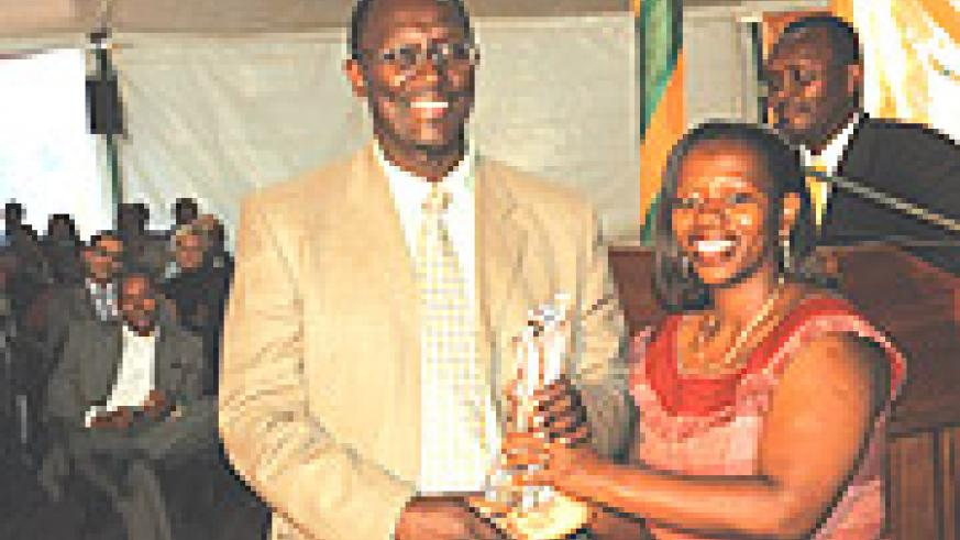 MTN's Rugege (L) receives the company's trophy for Best Over all Exhibitor from Commerce Minister, Monique Nsanzabaganwa at the closing ceremony. (Photo/ J.Mbanda).