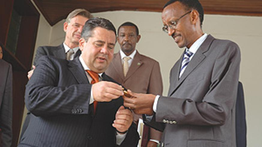 German Minister Sigmar Gabriel (L) giving President Paul Kagame a flash disk as a present at Village Urugwiro yeterday. (Photo/ G.Barya)
