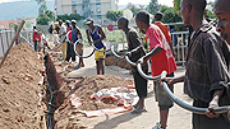 Workers laying optic fibre cable in Kigali City ( File photo)