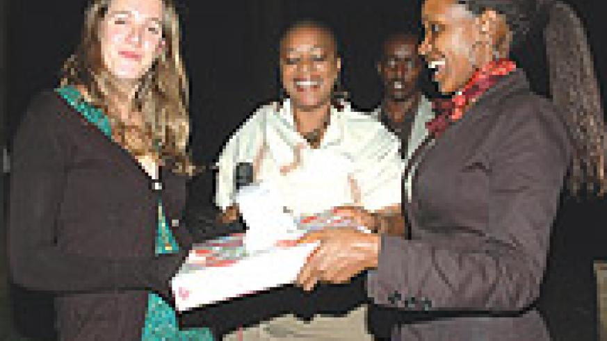 Kitty Llewellyn (L) receives a gift from The New Times' Managing Editor, Grace Kwinjeh (C)