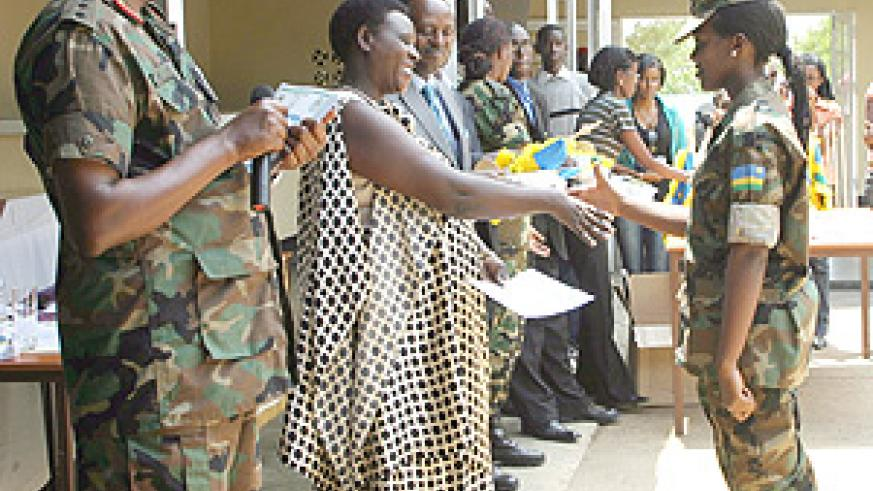 A Student receives  a certificate from the Education Minister Daphrose Gahakwa upon completion of Ingando at Gako Military Academy yesterday. (Photo / S. Nkurunziza).