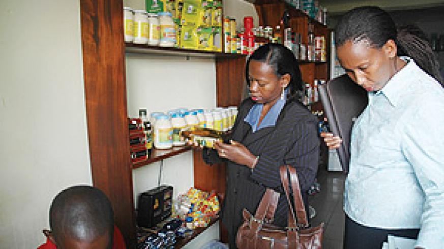 Commerce Minister Monique Nsanzabaganwa (L) closely looks at the expiry date of some items in a shop during the inspection exercise yesterday. (Photo J Mbanda).