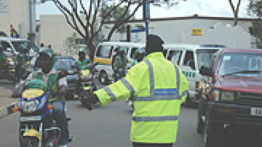 A Police man directs motocycles during the Road safety week that preceded Christmas. (Photo/ G.Barya).