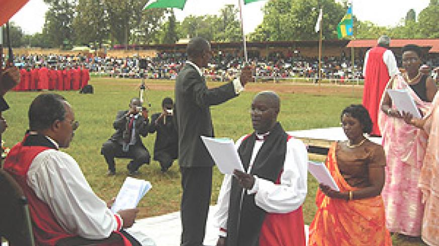 Rt Reverend Gasatura (kneeling) takes his Vows before Arch-Bishop Emmanuel Kolini(seated) in Huye on Sunday. (Photo/ P Ntambara).