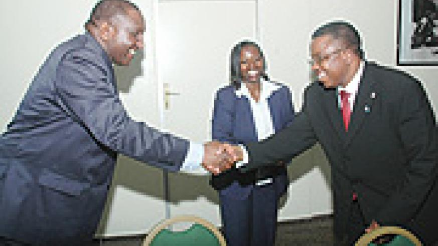 Ugandan State Minister of Tourism Serapio Rukundo (L) shakes hands with DR Congo Administrator for Nature Conservation Cosma Wilungula as Commerce Minister Minique Nsanzabaganwa looks on. (Photo/J Mbanda).