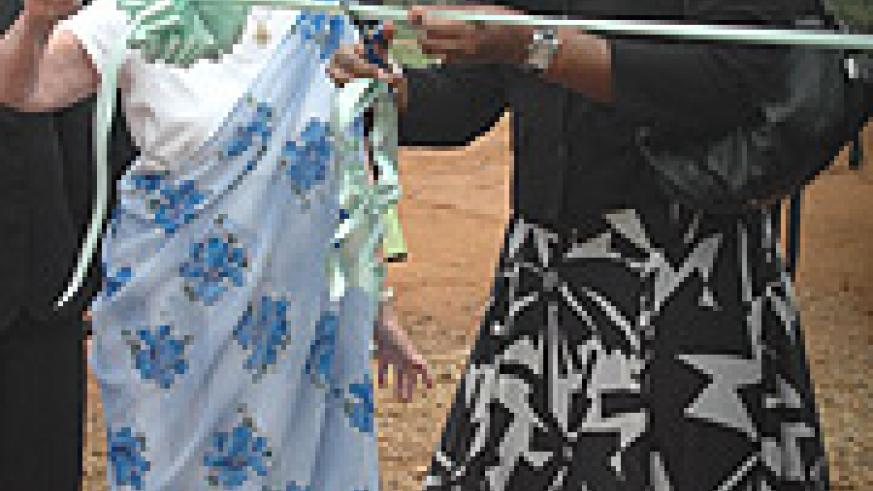 First Lady Jeannette Kagame with  Rosemary Jensen, the president the Foundation, cutting the ribbon to launch Rafiki Village in Bugesera  yesterday. (Photo/G.Barya).