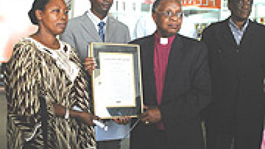 Bishop John Rucyahana with his wife displaying the Award from United States on Arrival at Kigali International Airport Yesterday. (Photo/ G.Barya).