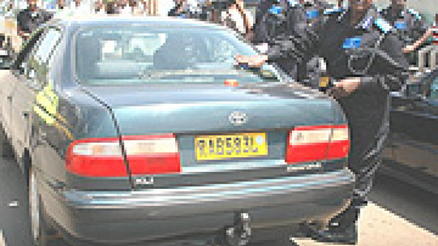 Acting Comissioner General of Police Mary Gahonzaire putting an anti corruption sticker on car to mark the beginning of the anti-corruption week yesterday. (Photo /G. Barya).