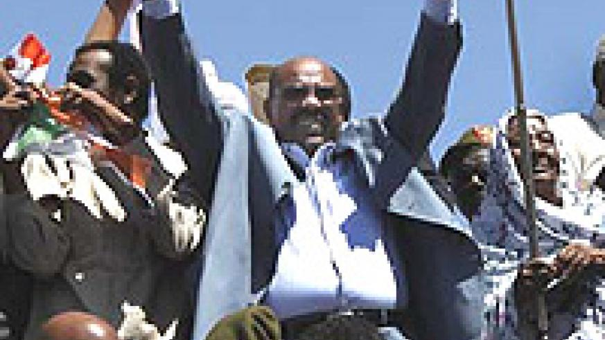 A defiant Omar al Bashir surrounded by supporters on his recent trip to Darfur.