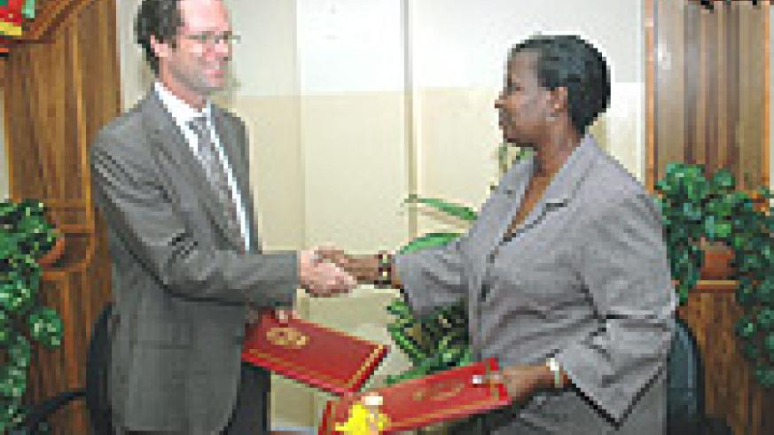 Foreign Affairs Minister Rosemary Museminari (R) and Herman Von Hebel shake hands after signing. (Photo J Mbanda).