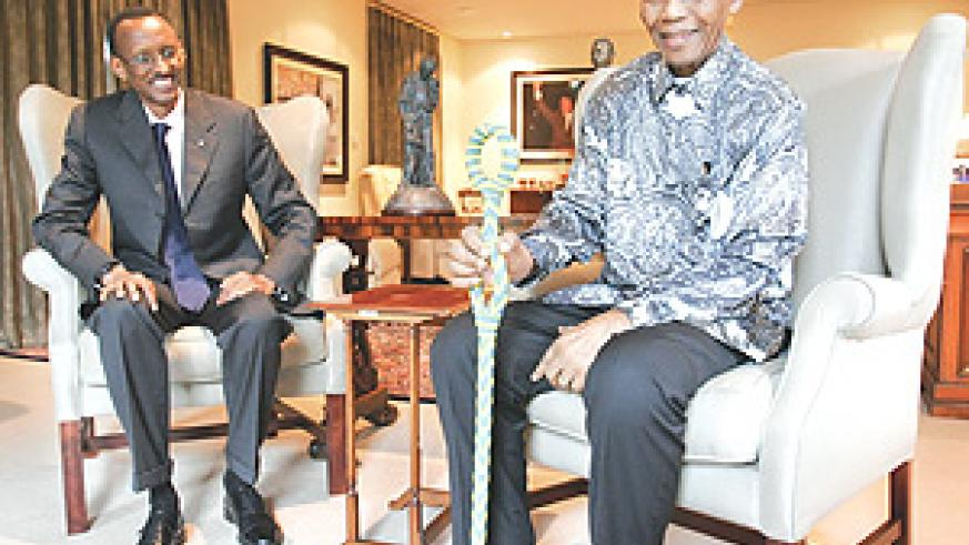 President Kagame with former South African President Nelson Mandela at the latter's residence yesterday. Mandela clutches a walking stick given to him as a gift by President Kagame. (PPU Photo).