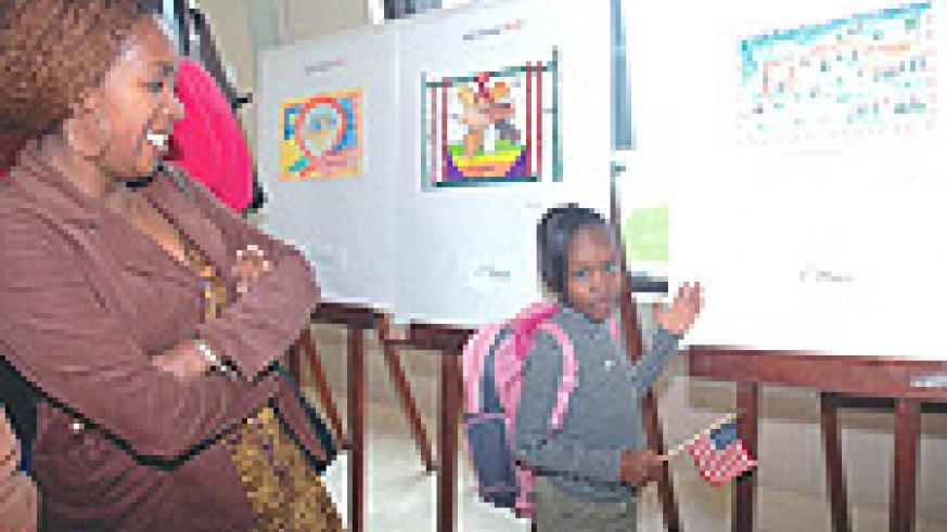 Laissa Umutesiwase points at her painting which took first place in the of 5-9  age group. (Photo/ J. Mbanda).