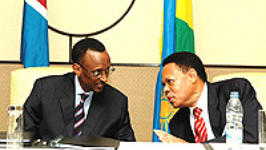 President Paul Kagame at the helm of the country's economy, shares a light moment with Juma Mwachu, EAC Secretary General during this year's EAC retreat. (File Photo).