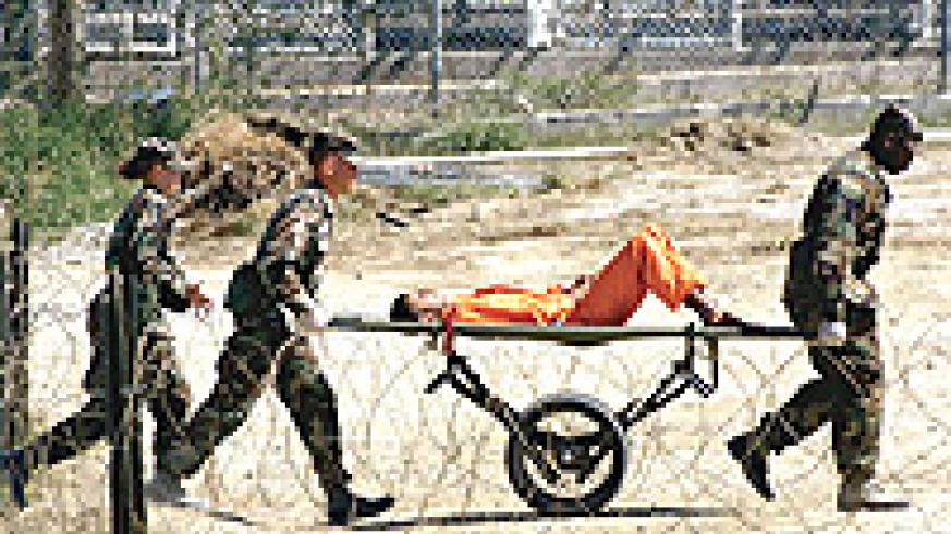 A prisoner at Guantanamo Bay being carted from one area to another like luggage.