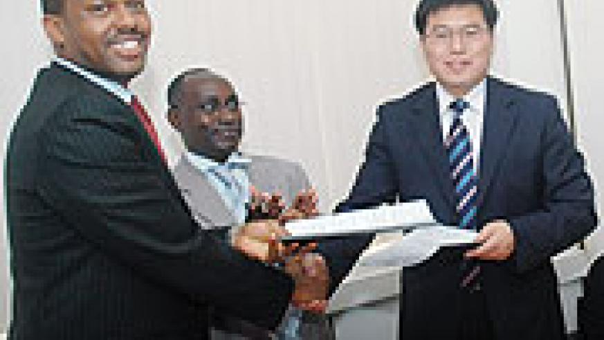 The Managing Director of Ultimate Concepts Leopold Mukama (L) shakes hands with Zhang Weize the General Manager B C E G after signing, as CSR Director General Henry Gaperi (2nd L) look on. (Photo/ J Mbanda).