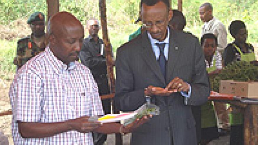 Aimable Gakirage, Director General of EAG (L) showing President Paul Kagame (R) imported French bean seeds.