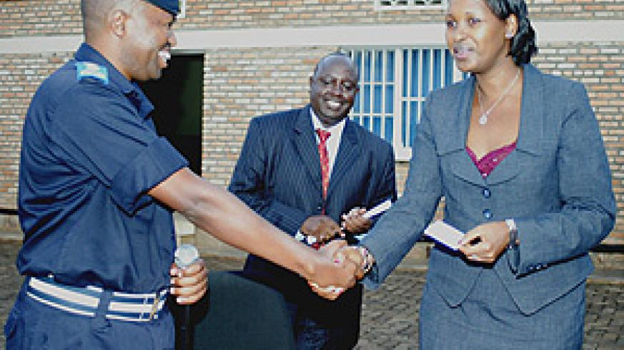 The minister of Infrastructure Linda Bihire receiving her Electronic Driving License from Traffic Police boss Robert Niyonshunti at the launch Yesterday. (Photo/ G.Barya).