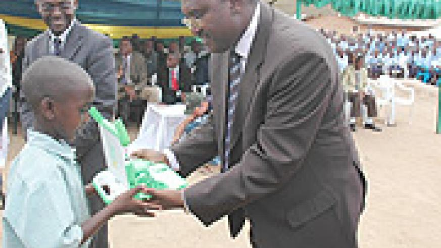 State Minister Theoneste Mutsindashyaka hands a laptop to a pupil as ICT  Minister Romain Murenzi looks on. (File Photo).