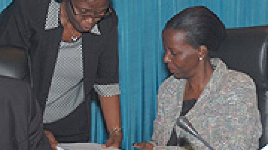 Hon. Bernadette Kanzayire (L) consults with Information Minister Louise Mushikiwabo at Parliament yesterday. (Photo/ J. Mbanda).