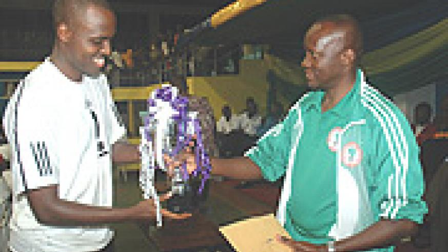 Minister Joseph Habineza hands the Volleyball trophy to APR team captain.