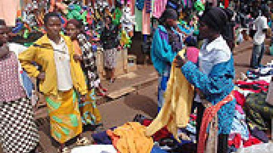 A business woman at Nyabugogo market convinces a customer to buy her clothes (File photo)
