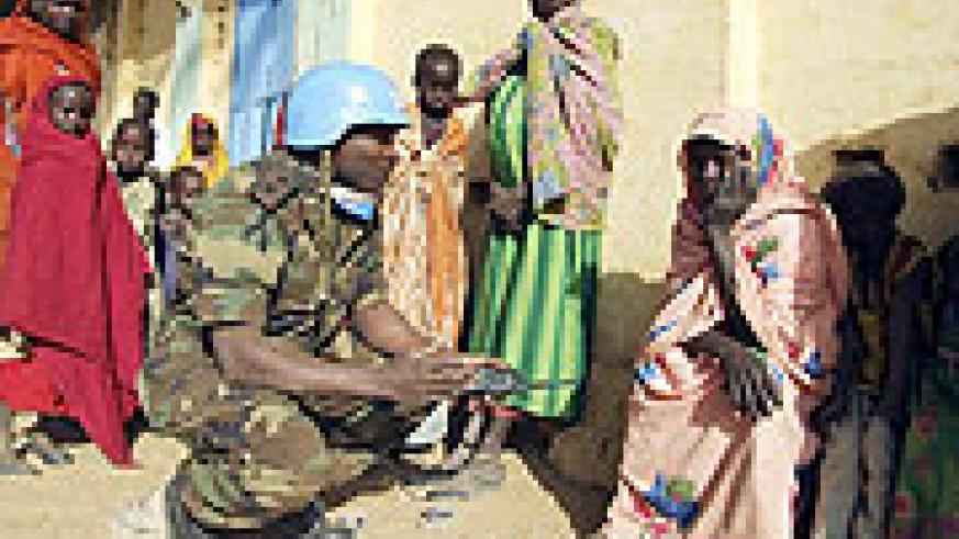 A UNAMID peacekeeper talks to displaced women in Darfur